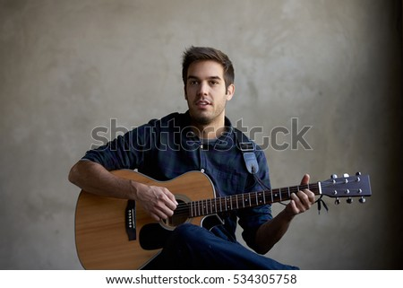 Shot of a young man holding his guitar and playing some music. #534305758