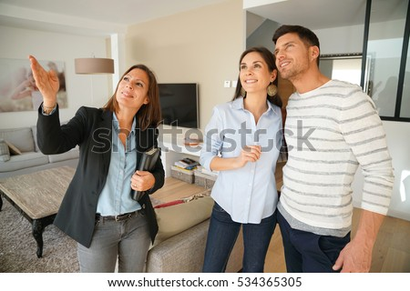 Couple with real-estate agent visiting house for sale Royalty-Free Stock Photo #534365305