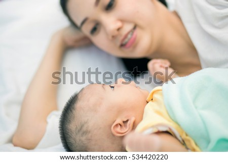 Happy young mom and baby lying on the bed #534420220