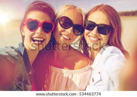 summer vacation, holidays, travel and people concept- group of smiling young women taking selfie on beach