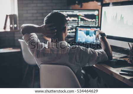 Developing new approaches. Rear view of young man in casual wear holding hand on the back of the head and working while sitting at the desk in creative office Royalty-Free Stock Photo #534464629