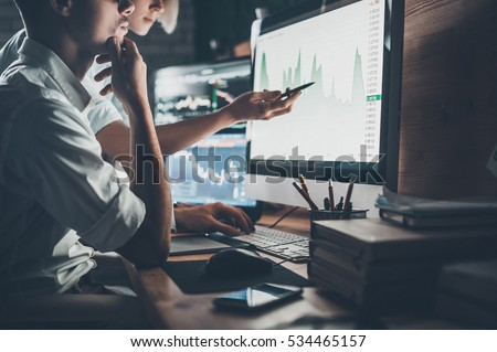 Analyzing data. Close-up of young business team working together in creative office while young woman pointing on the data presented in the chart with pen  Royalty-Free Stock Photo #534465157