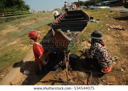 Siem reap, Tonle Sap lake, Cambodia desember 27, 2012: Woman and boy repairing a green boat on the shore of Lake Tonle Sap, Siem Reap, Kingdom of Cambodia #534544075