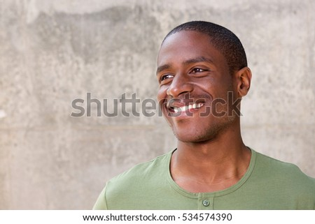 Close up portrait of young african american man on gray background smiling #534574390