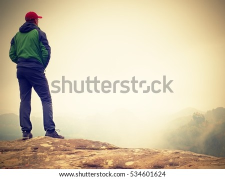 Young man in black sportswear is sitting on cliff's edge and looking to misty valley bellow. Autumn cold weather #534601624