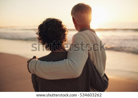 Rear view shot of retired couple watching amazing sunset. Senior man and woman standing together in the beach. #534603262
