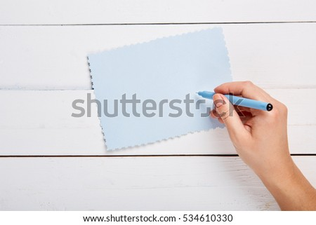 Hand with pen writing on a paper sheet. Overhead point of view. Modern flat design concept #534610330