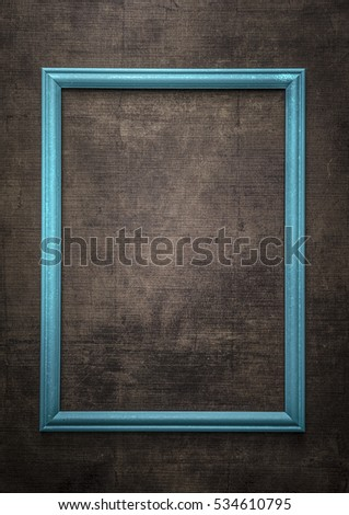 Blue  picture frame on old wooden wall, close up