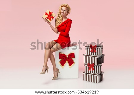 Beautiful sexy young blonde woman in red dress sitting on a big present, holding gift box. Christmas photo, presents #534619219
