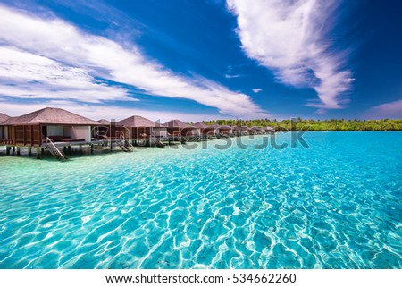 Luxurious water bungalows on tropical island with turquoise clear water.  #534662260