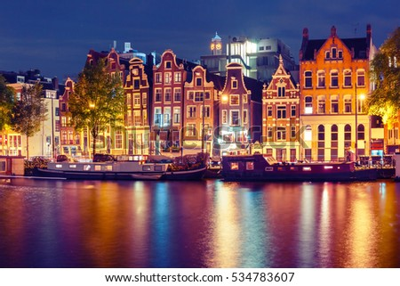 Amsterdam canal Amstel with typical dutch houses and houseboats with multi-colored reflections at night, Holland, Netherlands. Used toning #534783607
