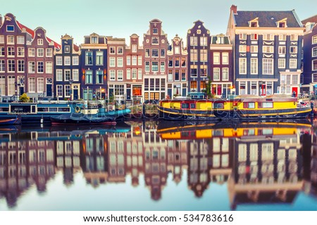 Amsterdam canal Singel with typical dutch houses and houseboats during morning blue hour, Holland, Netherlands. Used toning. #534783616