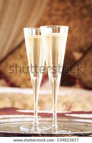 Two champagne glasses with oriental canopy bed at the background. Silver tray. Romantic concept. Valentines background. Arabian nights ambiance. Vertical, close up, glasses in the middle #534823657