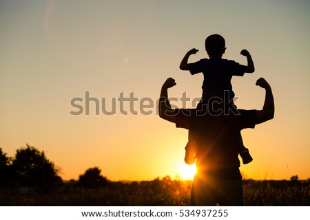 Father and son playing in the park at the sunset time. People having fun on the field. Concept of friendly family and of summer vacation. Royalty-Free Stock Photo #534937255
