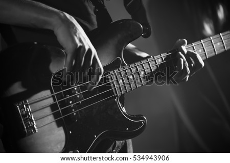 Closeup photo of bass guitar player hands, soft selective focus, live music theme, black and white #534943906