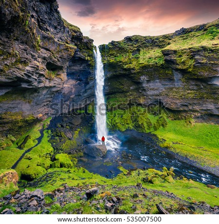 Colorful morning view of Kvernufoss waterfall with man standing on the rock. Majestic sunrise in south Iceland, Europe. Artistic style post processed photo. #535007500