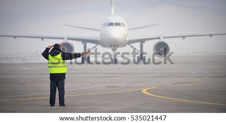 airport worker signaling #535021447