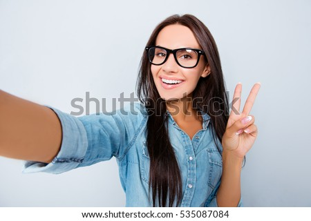 Happy woman in glasses with beaming smile making selfie and showing v-sign