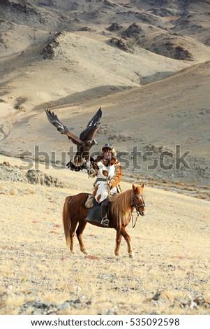BAYAN-ULGII, MONGOLIA - SEP 25: A senior mongolian horseman in traditional kazakh clothing with his altai golden eagle of village sagsai on September 25, 2016 in Bayan-Ulgii, Mongolia  #535092598