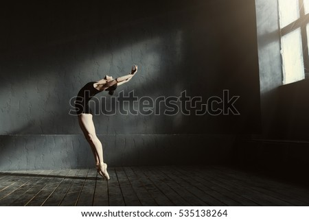 Flexible ballet dancer stretching in the dark lighted studio #535138264