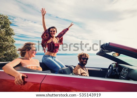 Group of happy young people in the red convertible. Vintage filter applied. #535143919