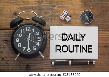 Daily Routine written on paper with wooden background desk,clock,dice,compass and pen.Top view conceptual #535155220
