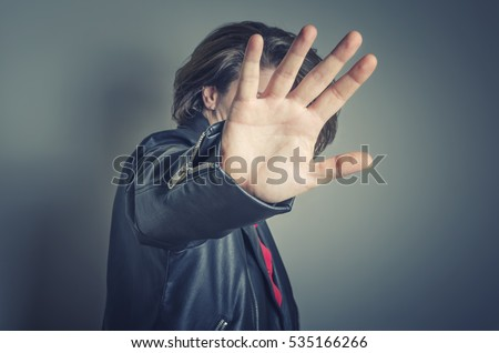 No pictures, please. Celebrity is hiding face with a hand from newspaper photographers.
