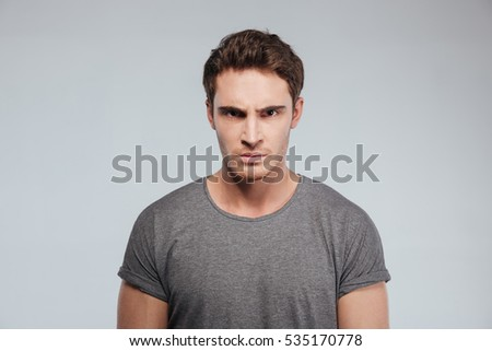 Close up of angry irritated young man looking camera over white background #535170778