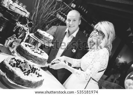 Black and white photo of newlyweds cutting tasty wedding cake
