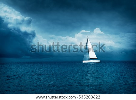 White Yacht Sailing in Stormy Sea. Dark Thundery Night Background. Dramatic Storm Cloudscape. Danger in Sea Concept. Cold Toned Photo with Copy Space. #535200622