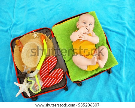 Cute baby and things for vacation in suitcase lying on blue bedspread. Holidays at sea with baby, concept #535206307