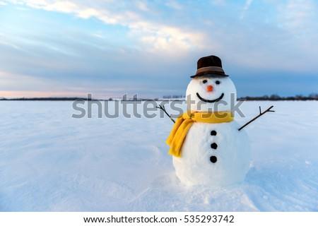 snowman on orange sunset background Royalty-Free Stock Photo #535293742