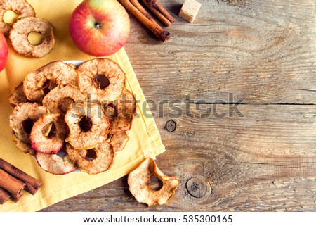 Organic apple cinnamon chips (slices) over rustic wooden background with copy space - healthy vegan vegetarian fruit snack or ingredient for cooking #535300165