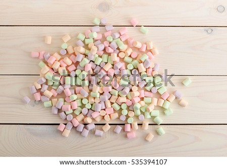 background from the scattered candy marshmallows on white wooden background - top view #535394107