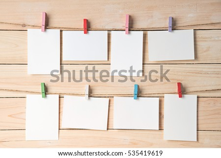 rows of empty photo frames hanging with clothespins on wooden background