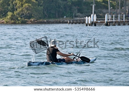 Man fishing in sea water from a  kayak  (AKA, Yak) with all the fishing gear ( rods, net & anchor).Photographed in Gosford Broadwater, New South Wales, Australia.