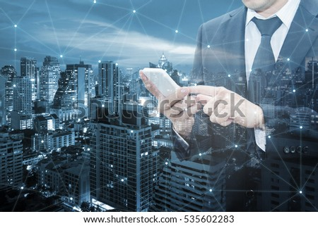 Double exposure of businessman touching with smart phone world business network connection and city center of business, Technology communication business and finance concept #535602283