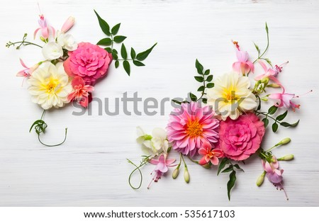 Festive flower composition on the white wooden background. Overhead view. Royalty-Free Stock Photo #535617103