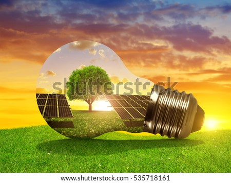 Solar energy panels in light bulb at sunset. The concept of sustainable resources. Royalty-Free Stock Photo #535718161