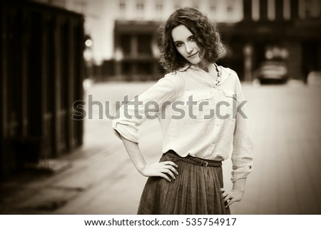 Happy young woman with curly hairs walking on city street Stylish fashion model outdoor #535754917