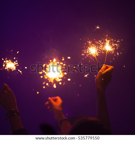Sparklers burn in people hands over dark purple background, holidays night party photo with soft selective focus #535779550