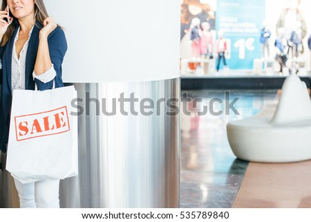 Crop shot of young elegant female using device in buying center.  #535789840