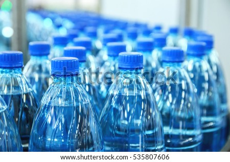Closeup on mineral water bottles in raw and lines Royalty-Free Stock Photo #535807606