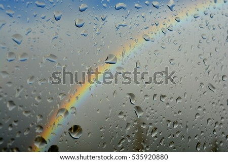 Rainbow seen from the window while it is raining. Raindrops on the window