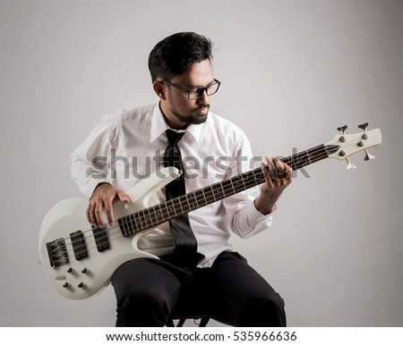 portrait of asian businessman playing guitar on the chair #535966636
