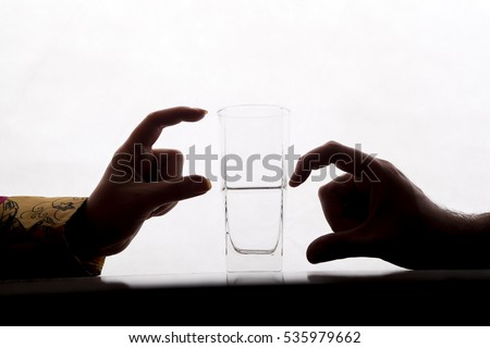 two couple are showing half full and half empty side of water glass with their fingers #535979662