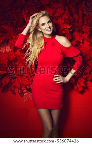 Beautiful young elegant woman in sexy red dress posing over red background with poinsettia holding. Christmas fashion photo