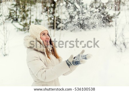 Christmas girl outdoor portrait. Girl throwing snow. Woman in winter clothes on a snow field. Toned picture