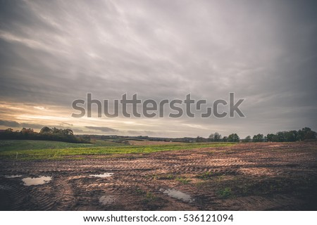 Landscape with wheel tracks on a muddy field in autumn in cloudy weather in off-road terrain