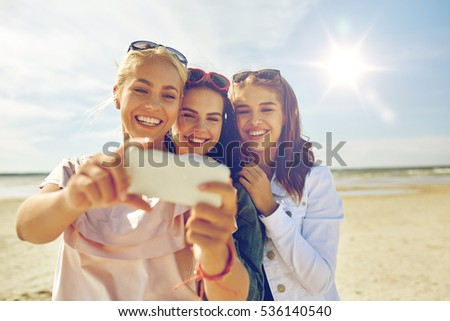 summer vacation, holidays, travel, technology and people concept- group of smiling young women taking sulfide with smartphone on beach